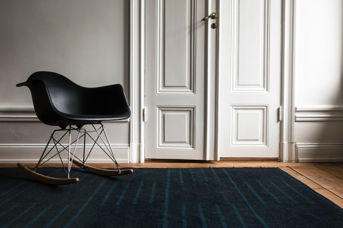 Classic in Black and Teal shown in an open room with a modern black rocking chair.