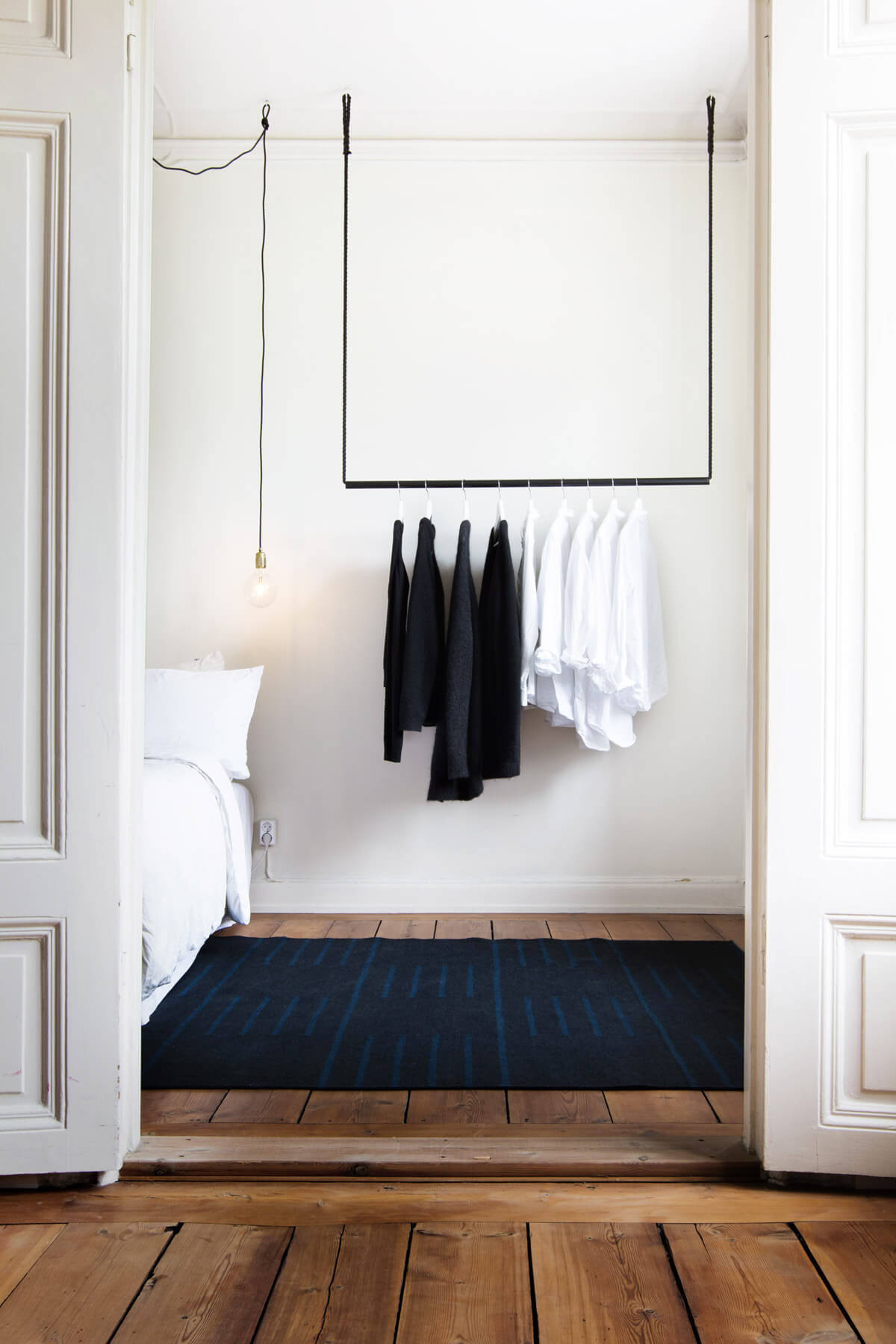Flatweave rug Classic in Black displayed in a white turn of the century bedroom.