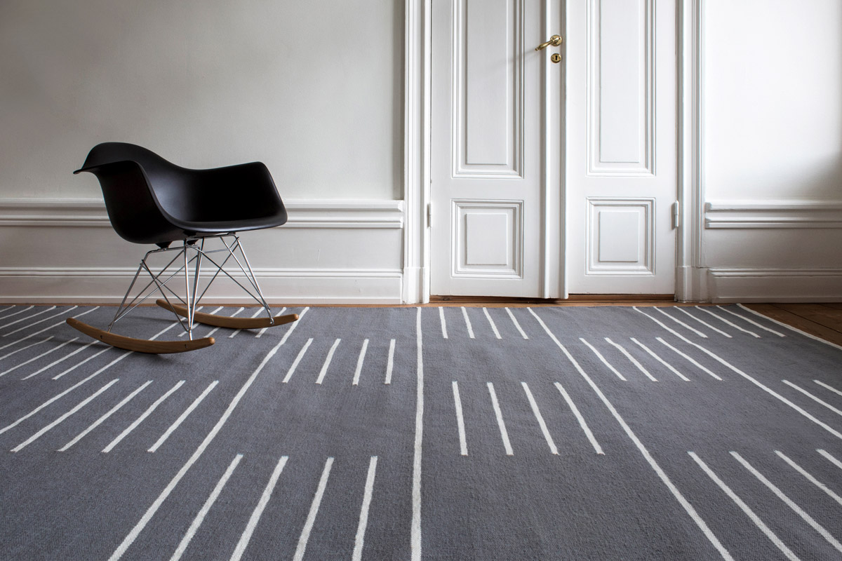 Stripes in Gray shown in an open room with a modern black rocking chair.