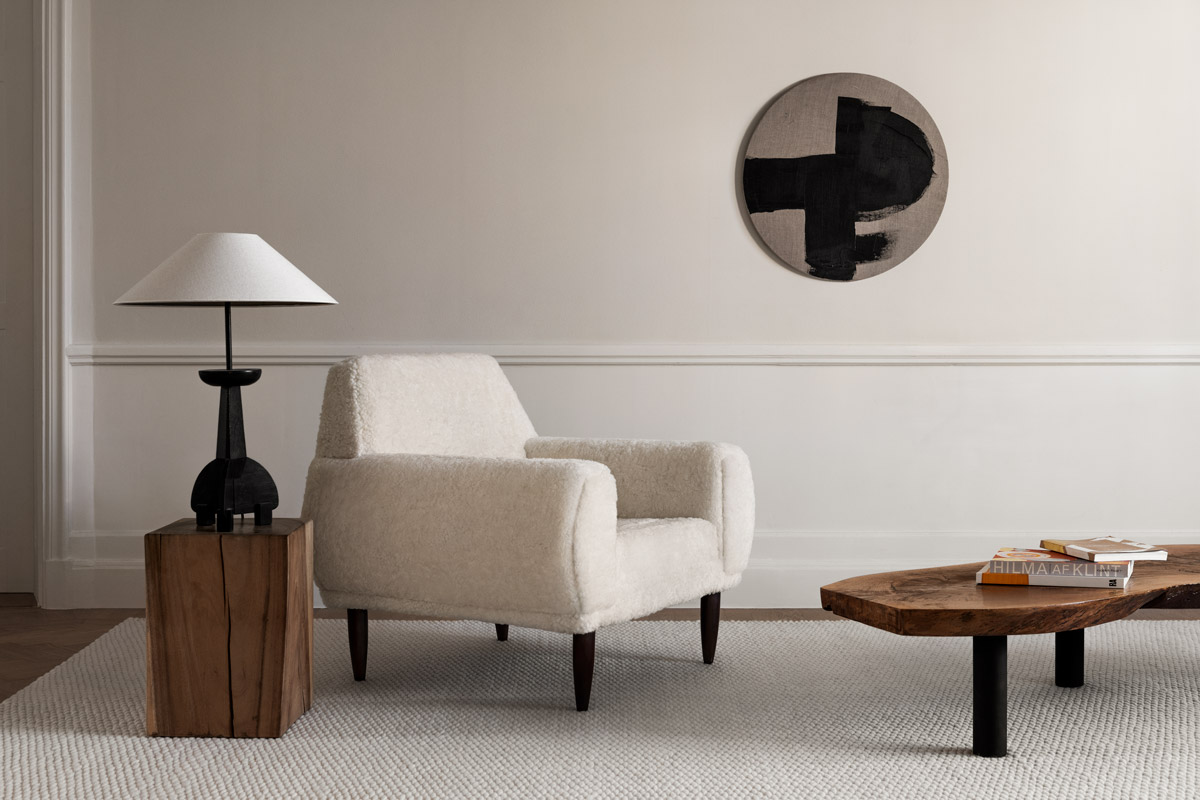 Dunes in color Cream shown in a light, classy apartment. Styled with a white sheep fur armchair and wooden coffee table.