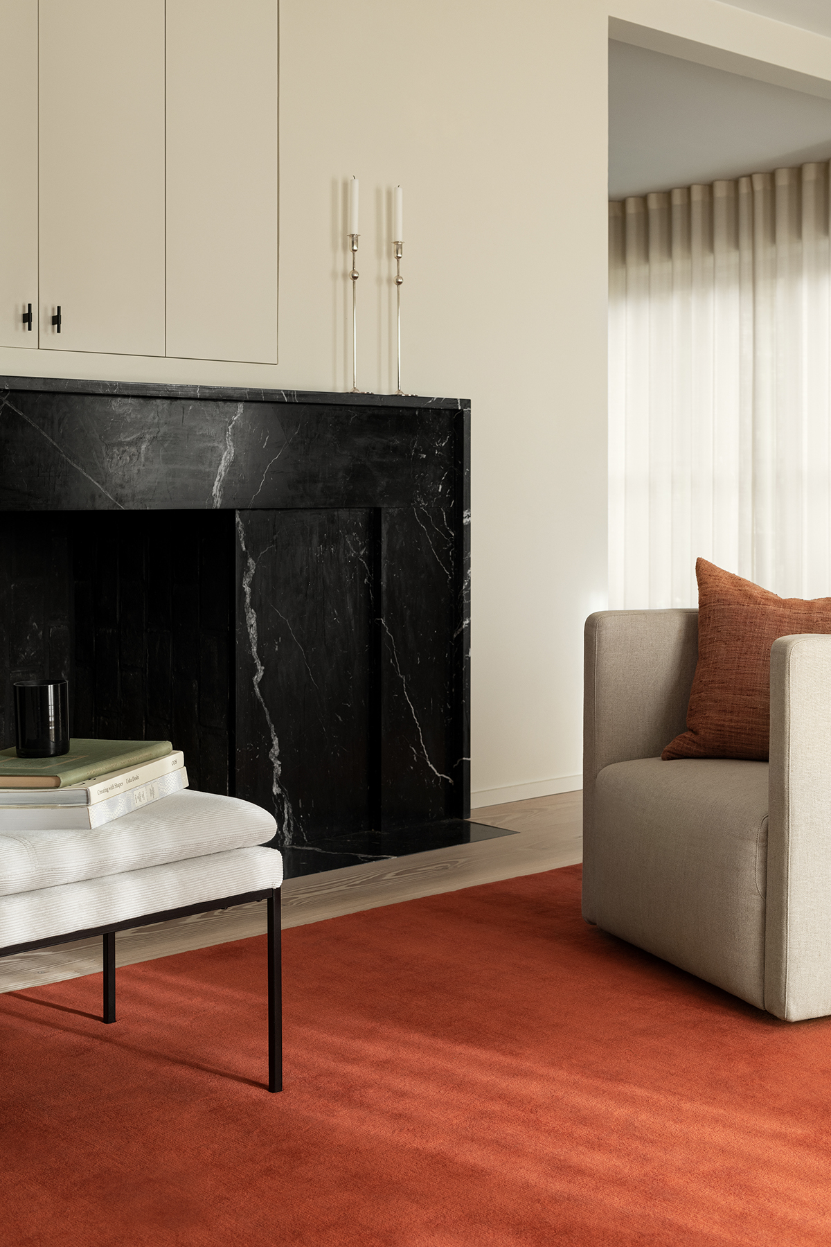 The Grand rug in Brick Red shown in a classy apartment with a large fireplace in black stone.