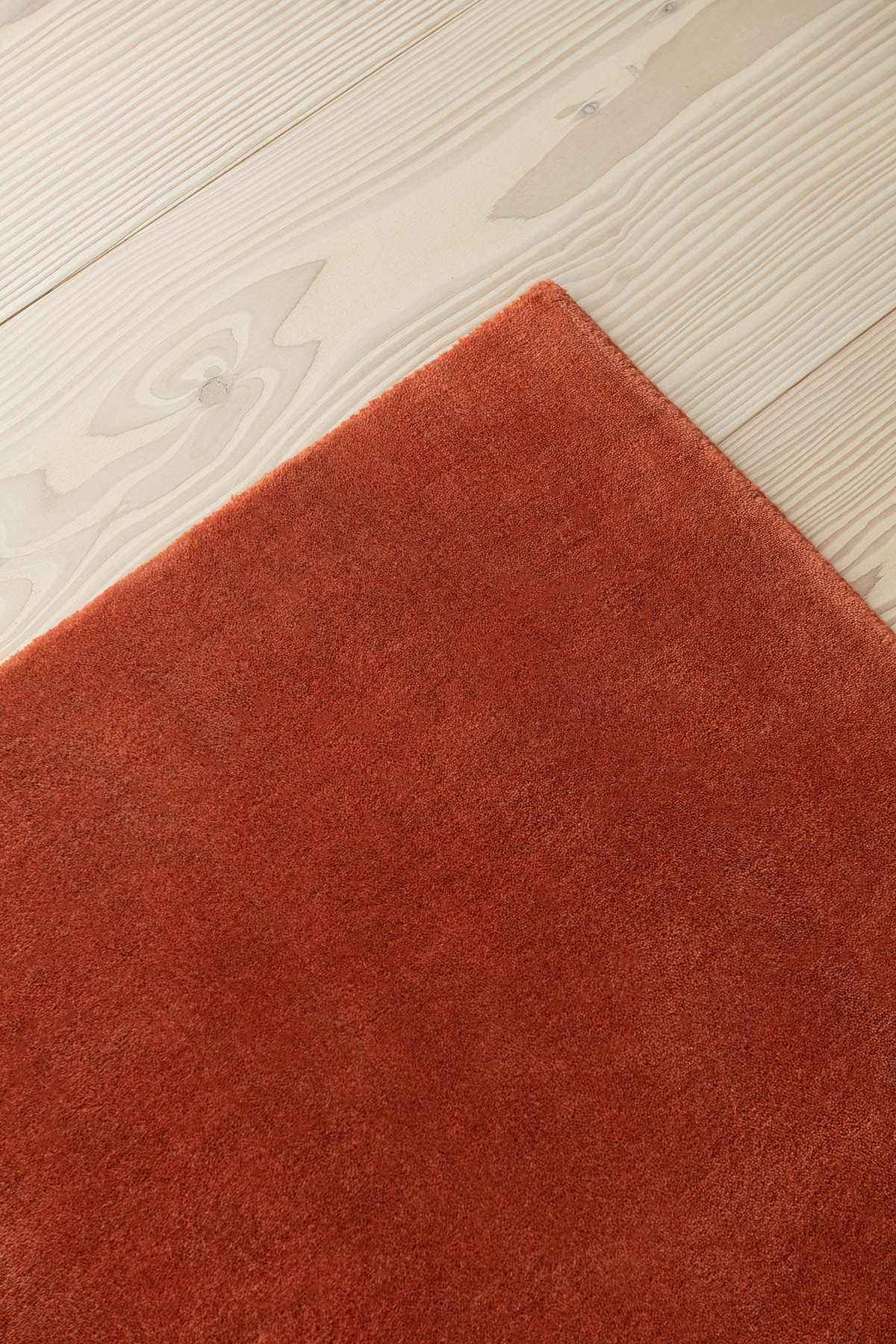 Close up of a corner on a Grand rug in Brick Red.