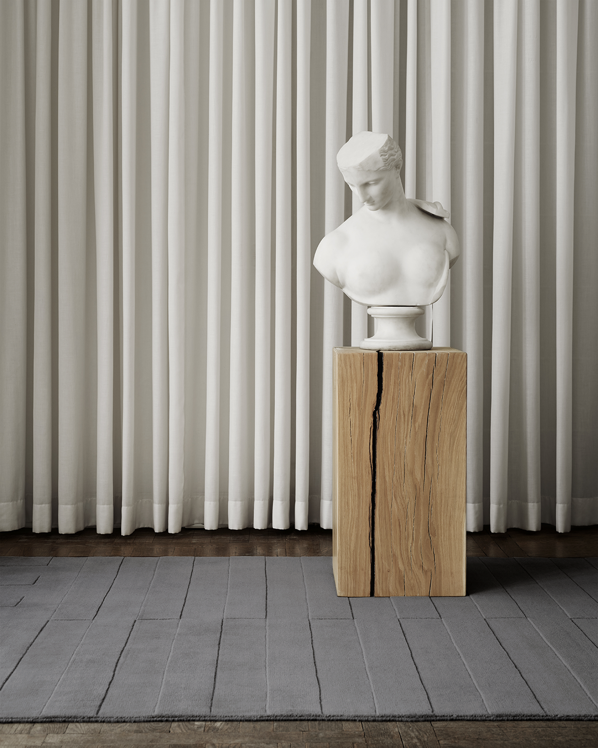 The Lux 2 rug in Gray displayed together with a marble bust on a wooden pedestal.