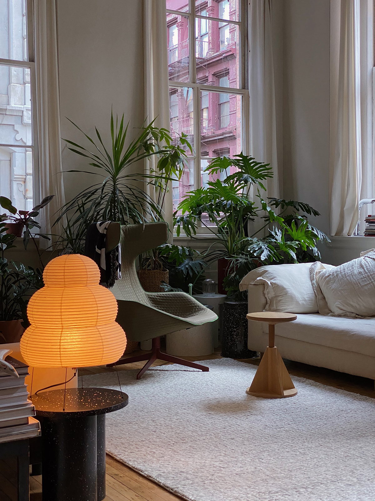The Dunes rug in the color Melange in an inspiring New York loft, decorated with green plants and design furniture.