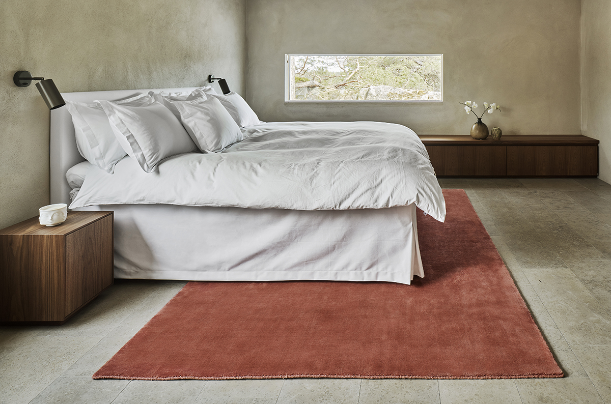The Grand rug in Brick Red shown in a modern, minimalistic bedroom.