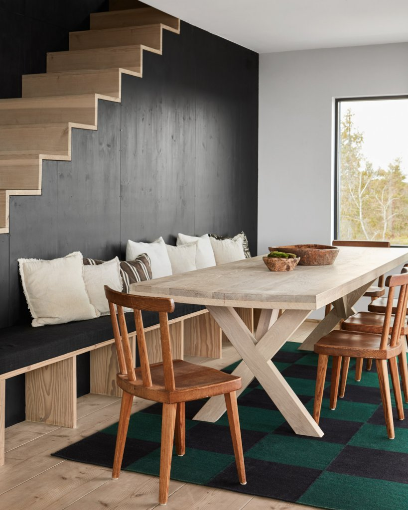 The Square flatweave rug photographed in a dining room setting in a summerhouse in the Stockholm Archipelago.