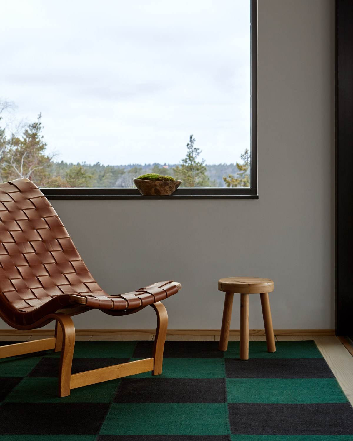 The Square green/black flatweave rug with a vintage armchair and stool.