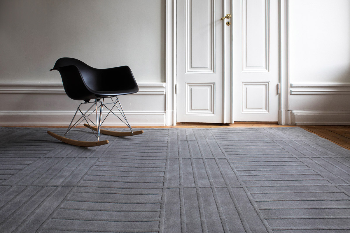 Lux 1 in color Gray shown in an open room with a modern black rocking chair.