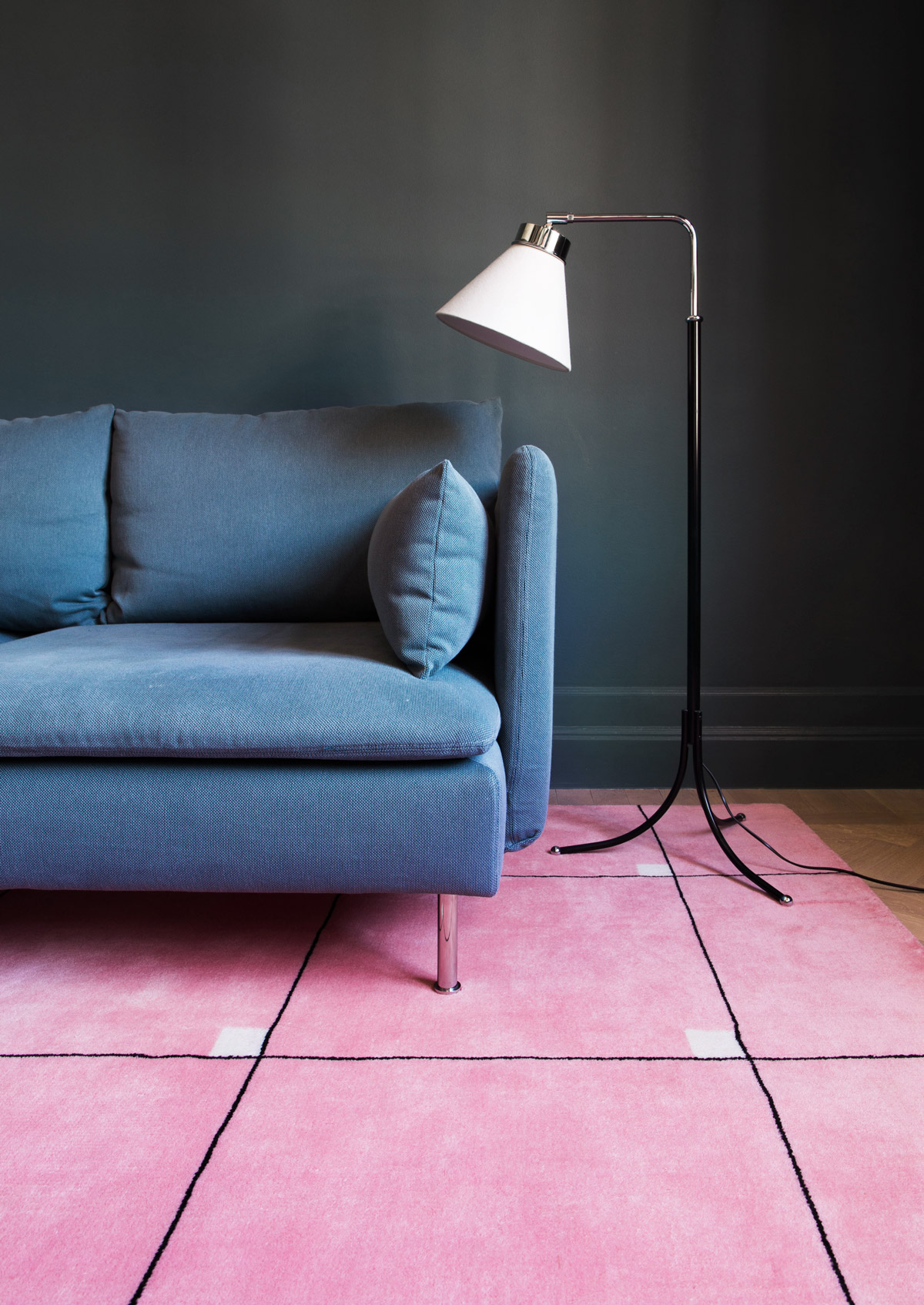 Plush rug Modern in color Pink shown together with a blue couch and a floor lamp.