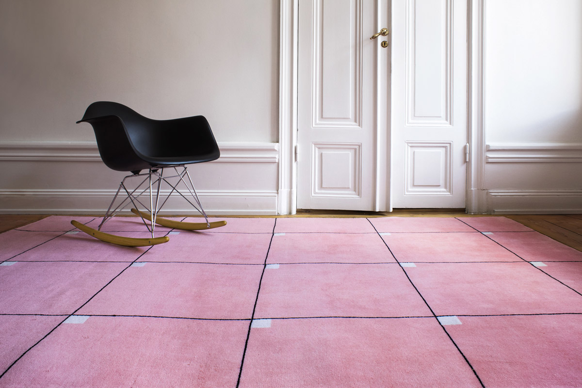 Modern in color Pink shown in an open room with a modern black rocking chair.