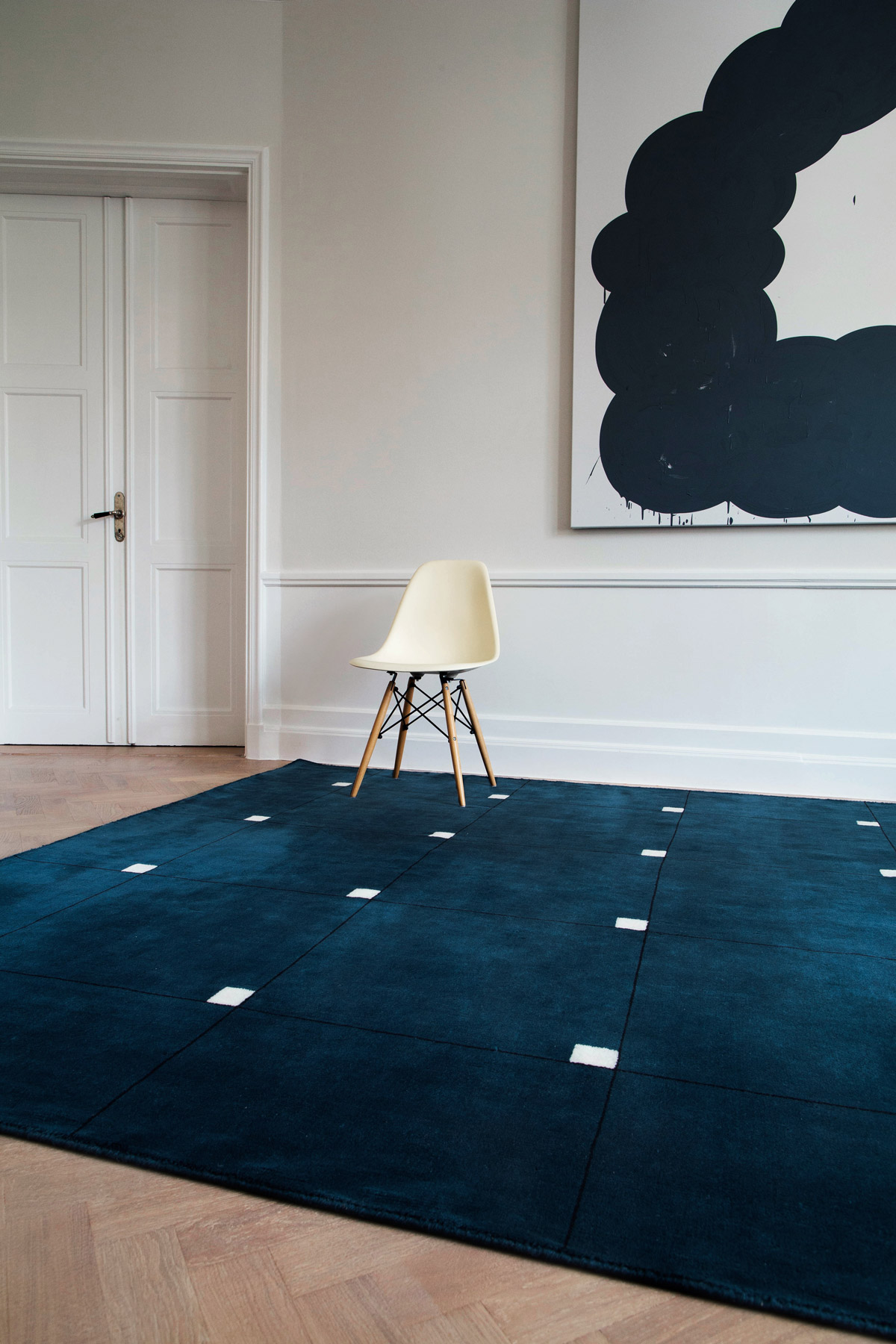 Plush rug Modern in Teal displayed in a bright, sunny living room decorated with a white chair.