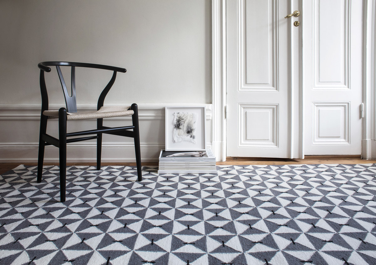 Mosaik in color Gray shown in an open room with a black wishbone chair.
