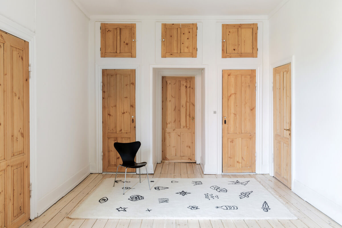 Shaggy rug Nomad in cream displayed in a white room with multiple wooden doors.