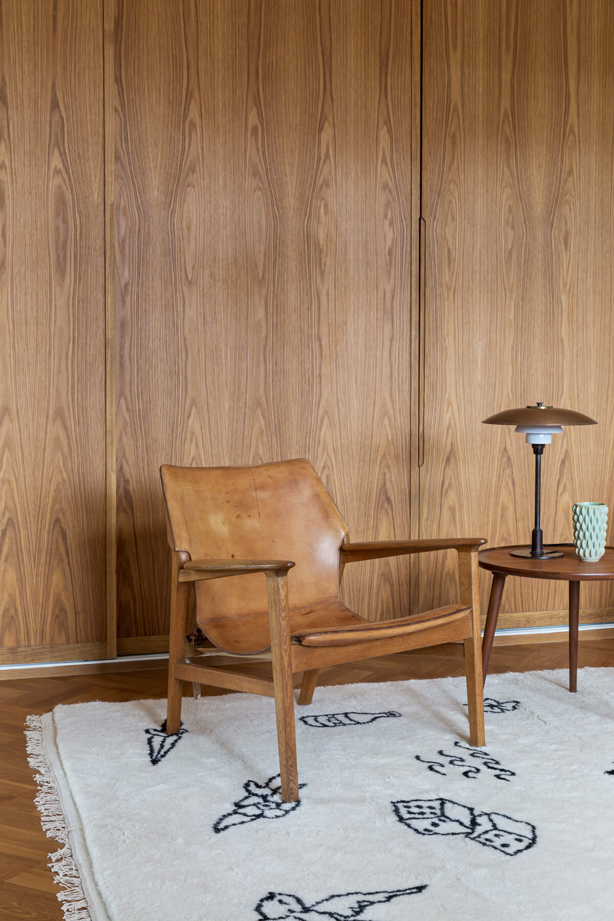 Shaggy Nomad in color cream styled with a leather and wood armchair.