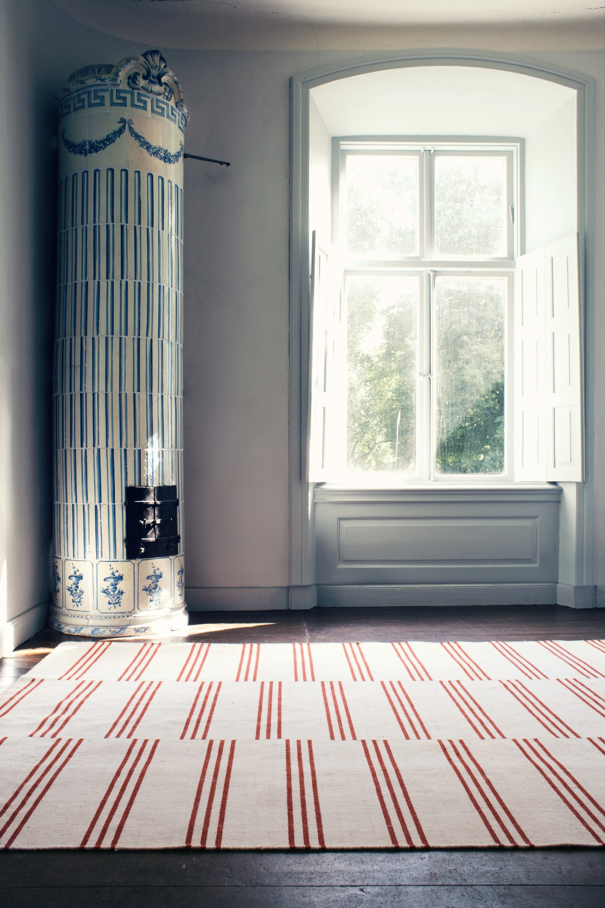 Stripes in Pink and Red in a sunny room with a beautiful tiled stove.