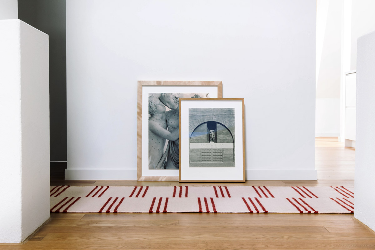 Stripes in Pink and Red laying in a white room with two frames on the floor.