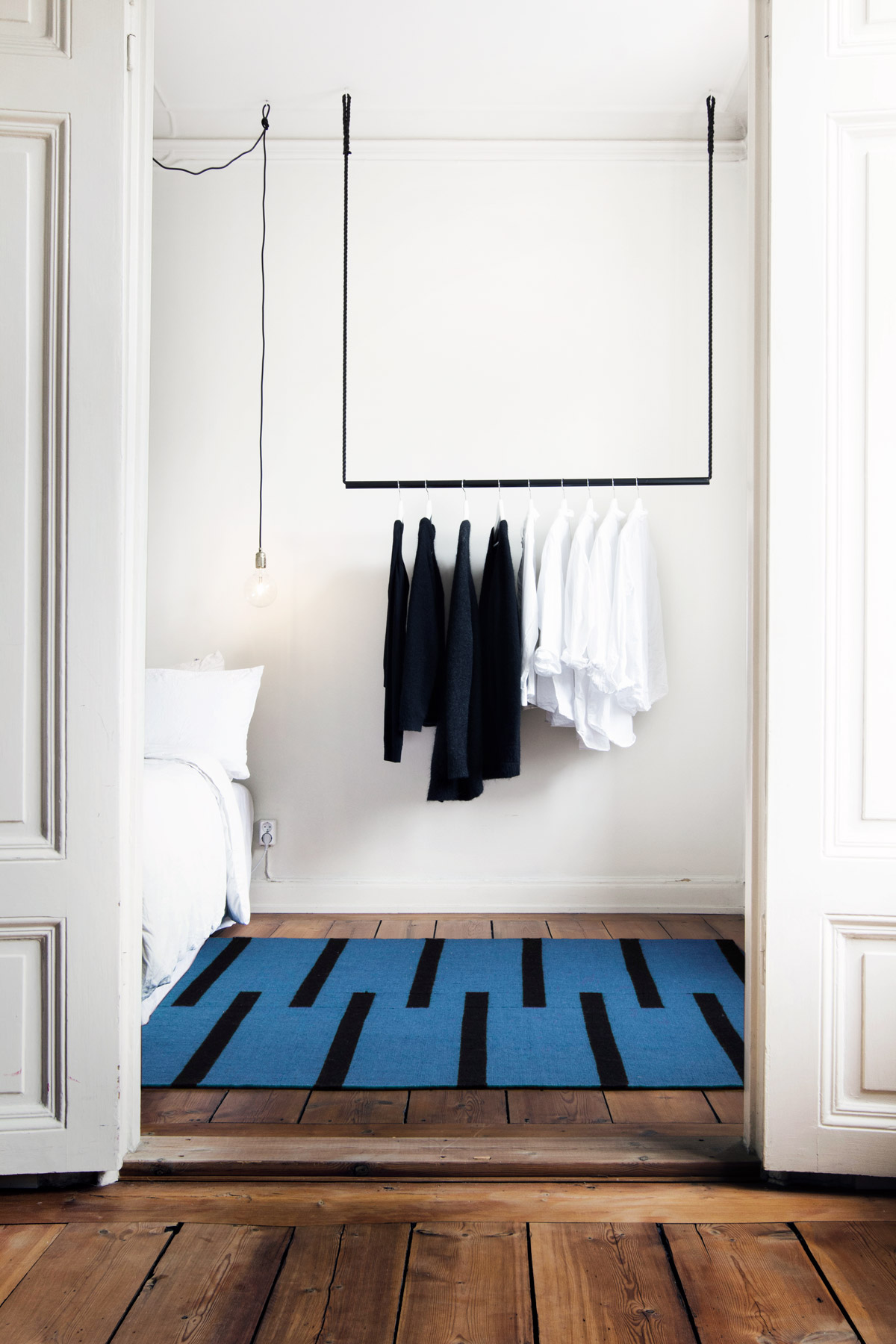 Flatweave rug Tiger in blue displayed in a white turn of the century bedroom.