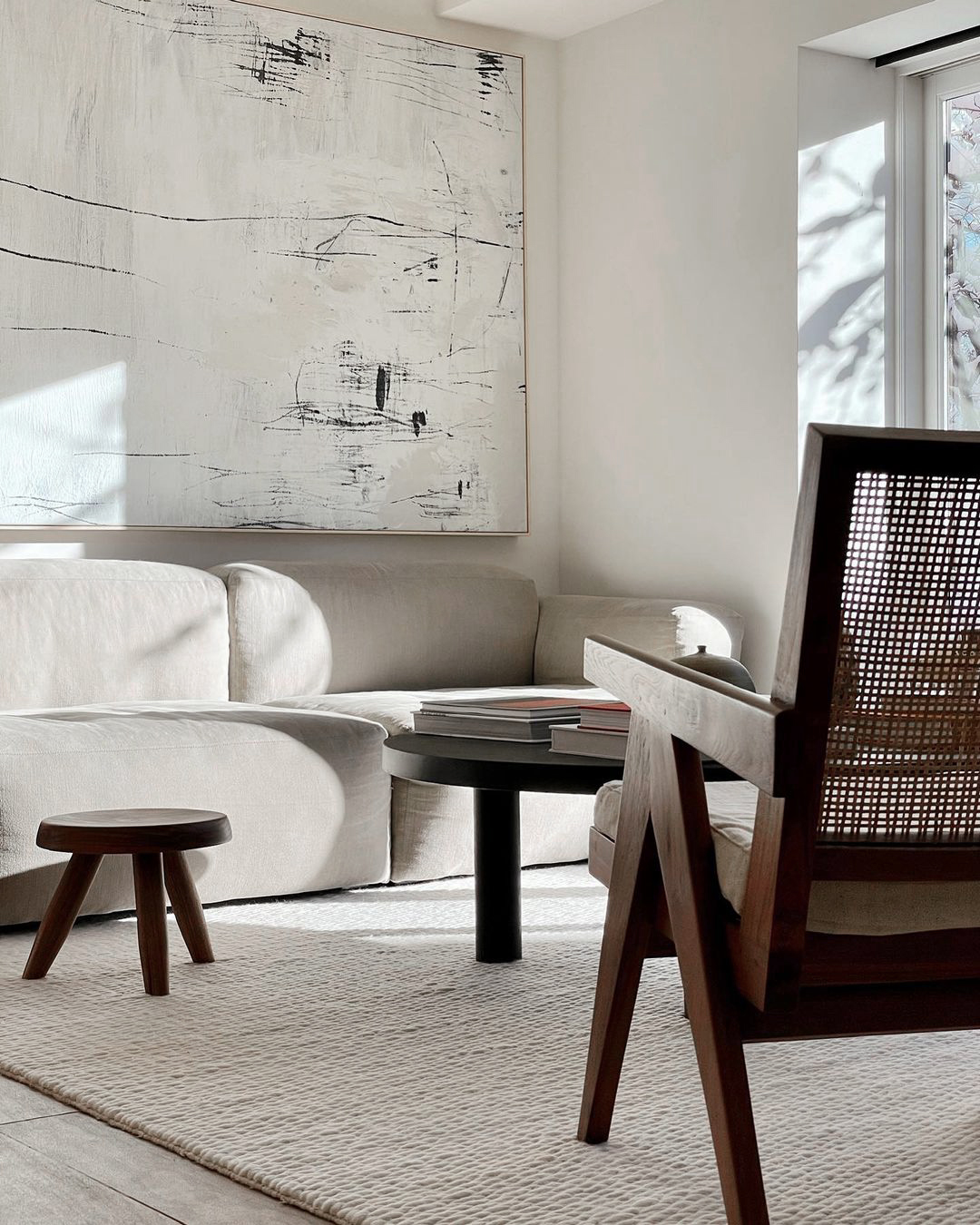 The Cream colored Dunes rug in a bright, sunny apartment together with a white sofa as well as dark wooden furniture.