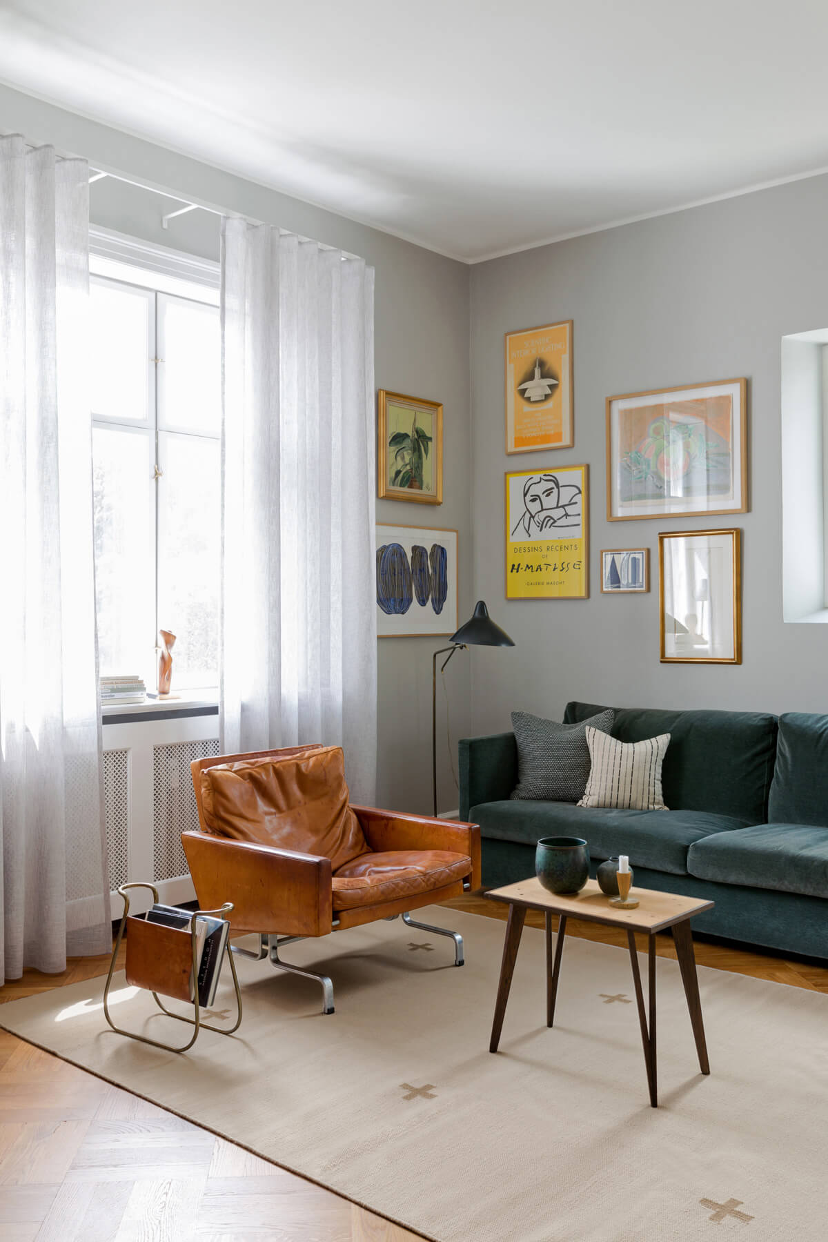 Plus in color sand displayed in an inspiring living room with a teal sofa, leather armchair and art on the walls.