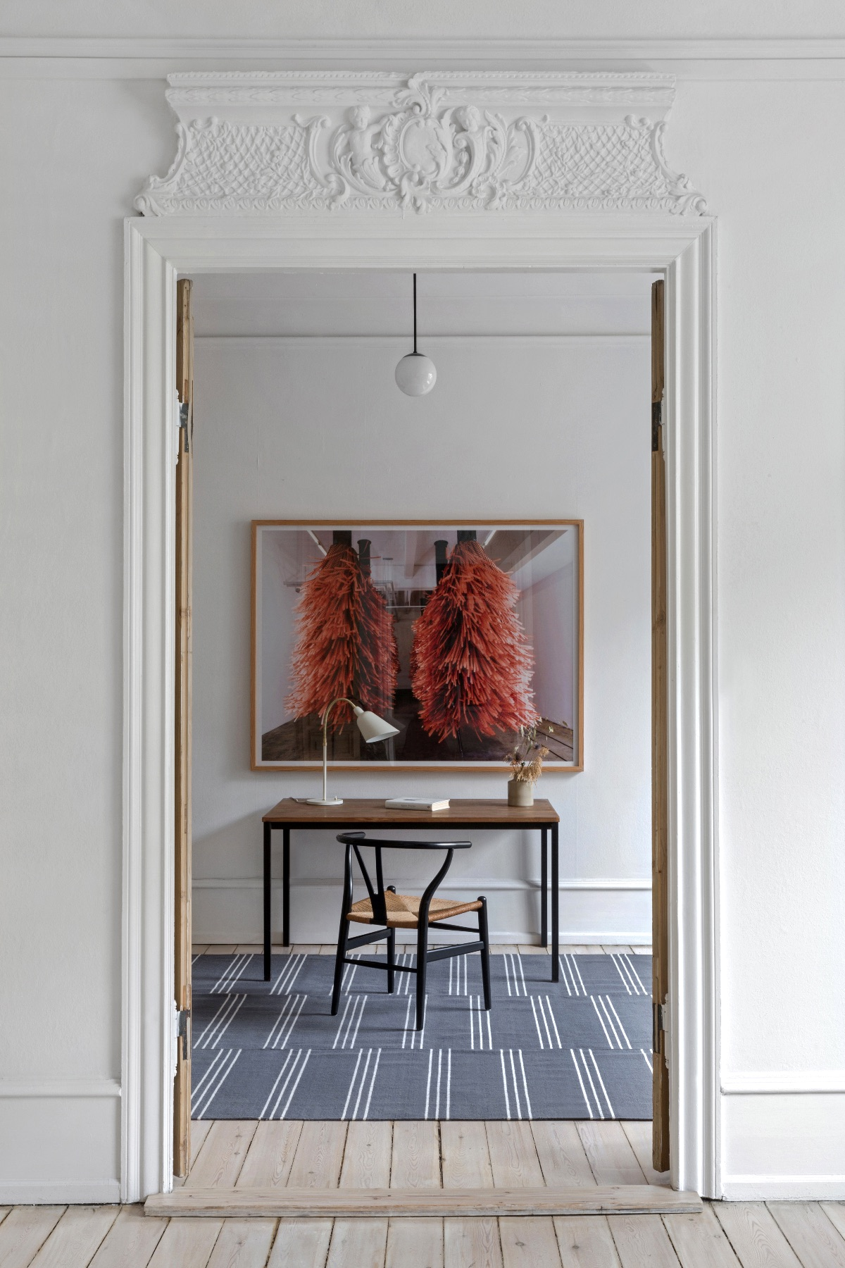 Stripes rug in color Gray styled with a desk and wooden chair infront of a large photo art piece.