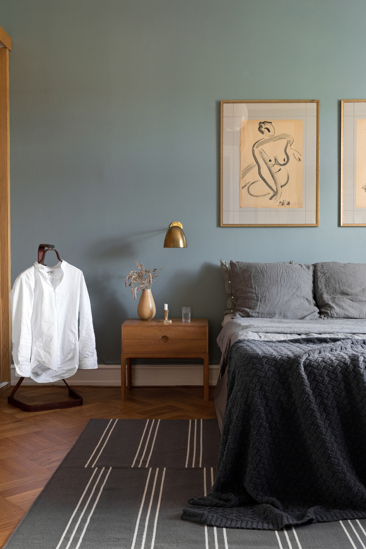 Flatweave rug Stripes in color Gray styled in a cozy bedroom with teal walls.