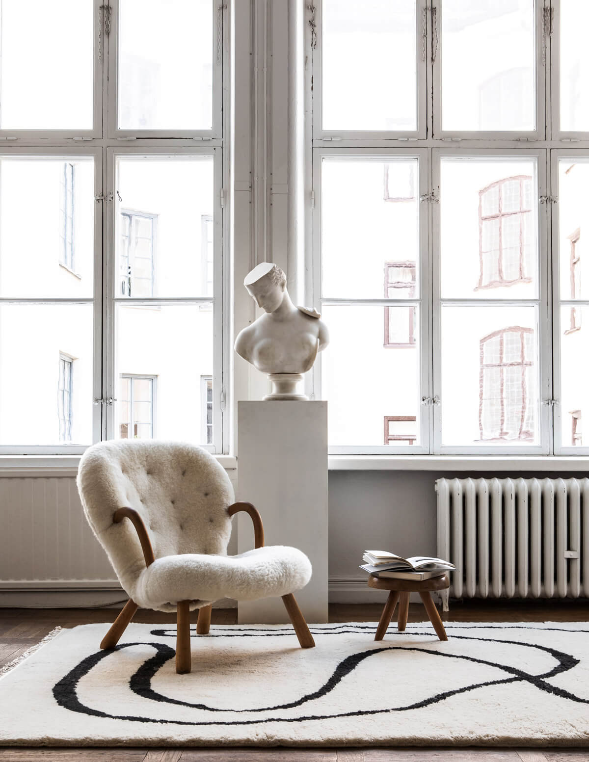 Shaggy rug Simple Object 18 in Dusty White shown in the Nordic Knots atelier. Styled with a sheep fur armchair and marble bust.