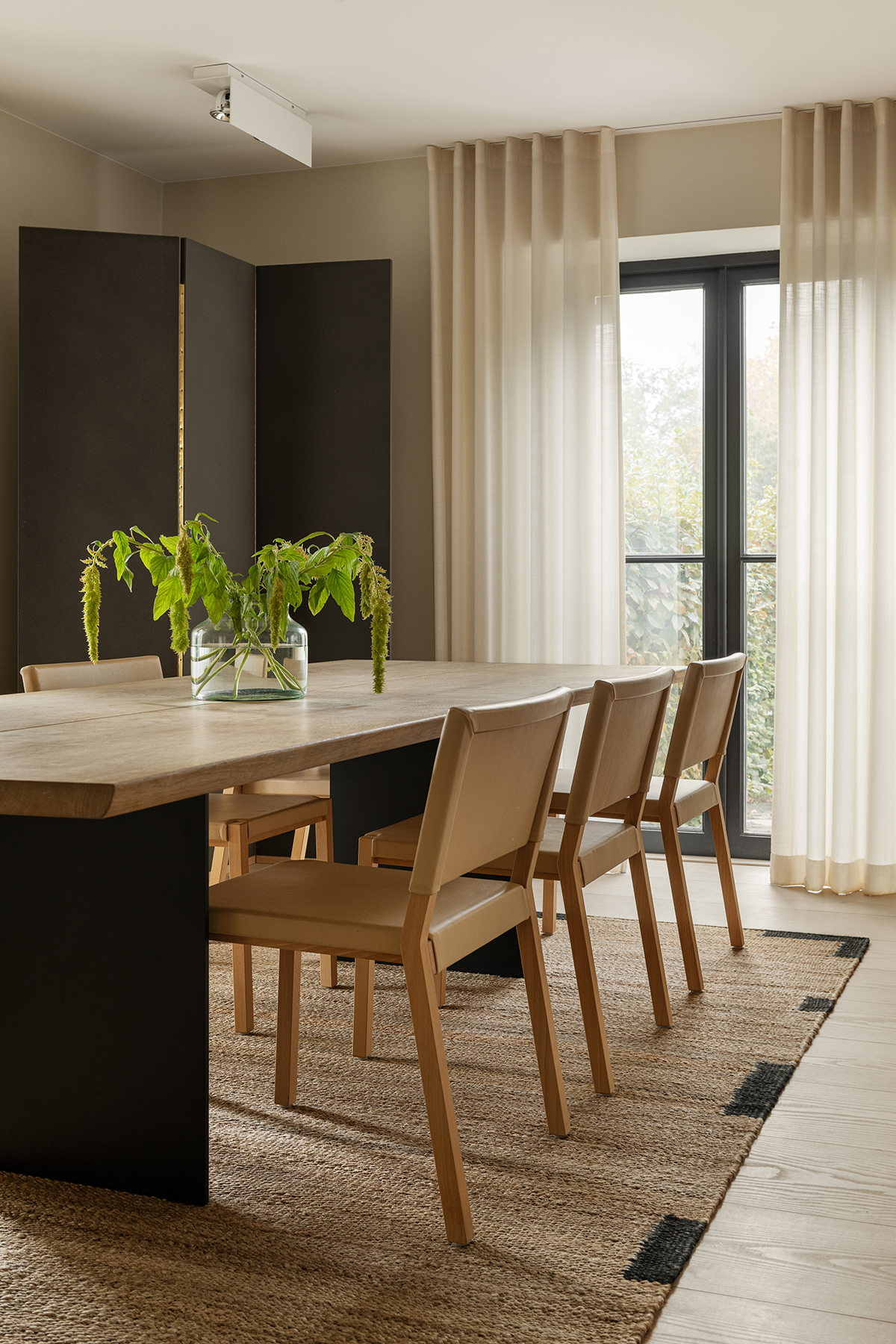 The Jute Edge rug in Black in a sunny dining room with a large dinner table as well as chair in wood on top of it.
