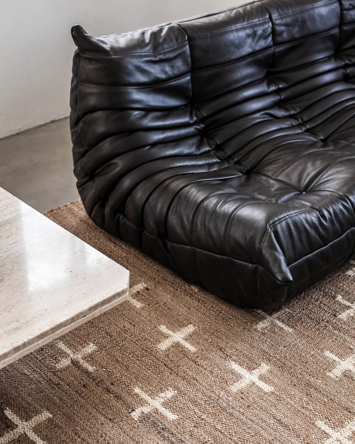Close up Jute Cross in Cream styled with a leather Togo sofa.