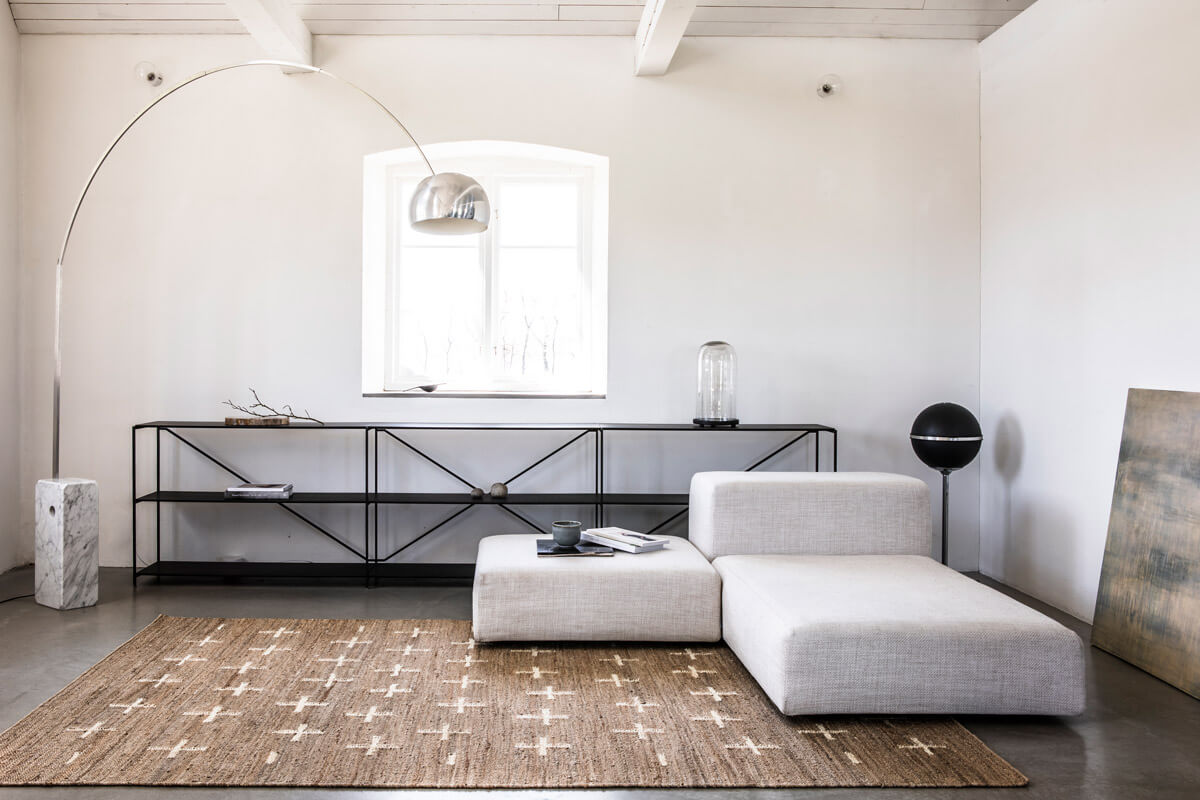 Jute Cross in Cream displayed in a sunny, contemporary barn house together with a light gray sofa and large floor lamp.