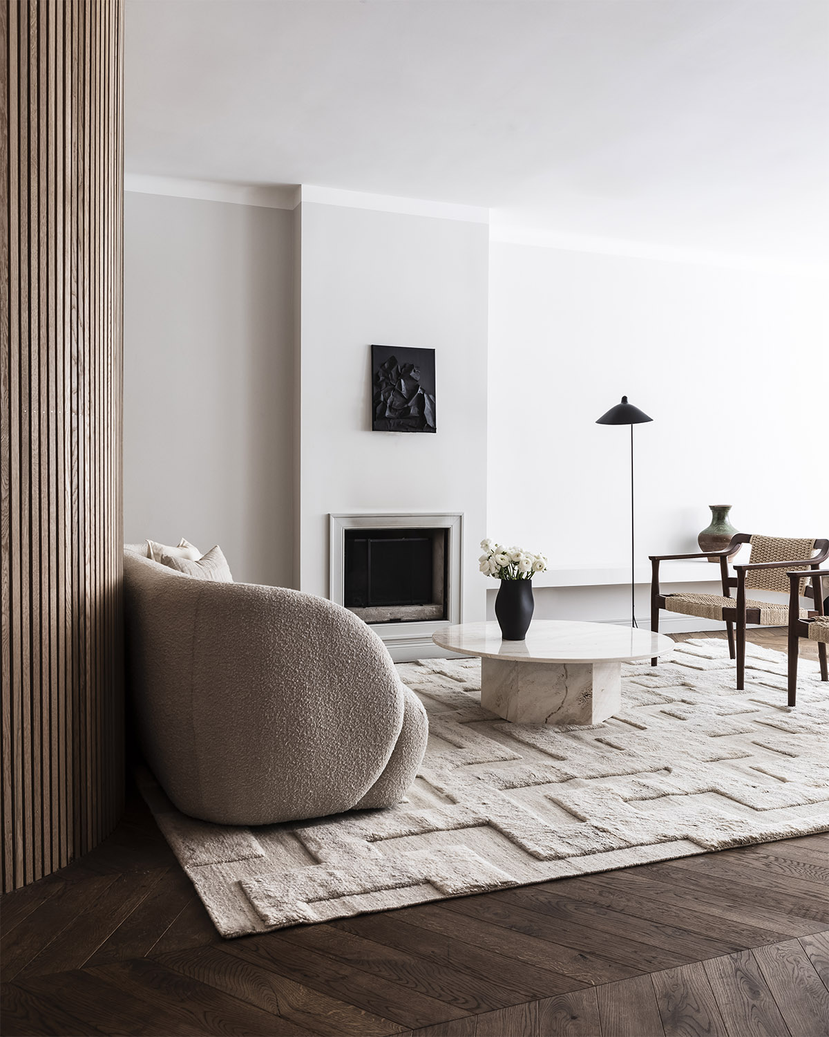 Boho rug in the color Cream Mix shown in a bright living room together with a stone table and a white rounded sofa.