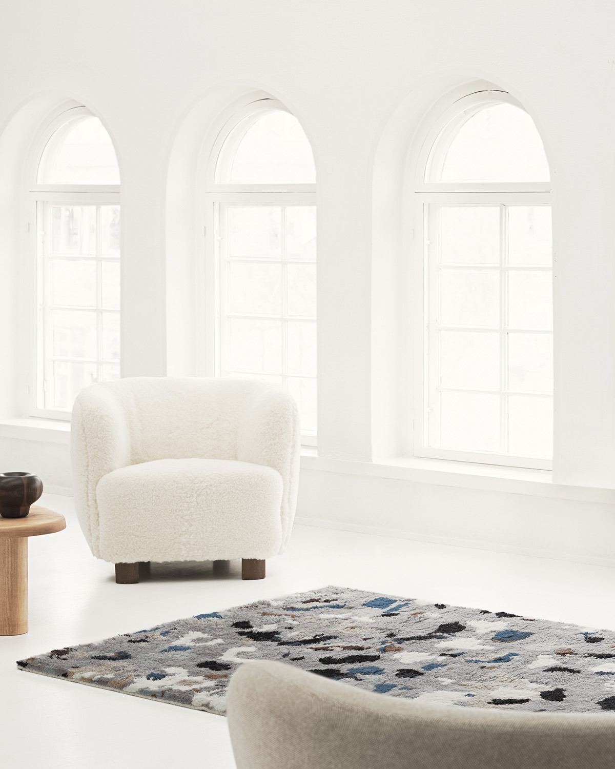 Shaggy Archipelago in the color Gray is displayed in a white, gallery-like setting with arched windows in the back.