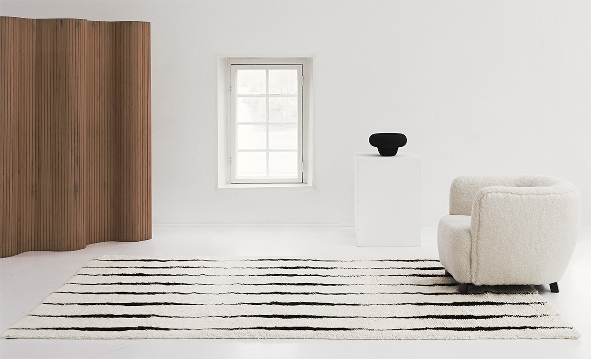 The shaggy Cream colored rug Fjord is displayed in a white, gallery-like setting together with a white sheep fur armchair and a wooden room divider.