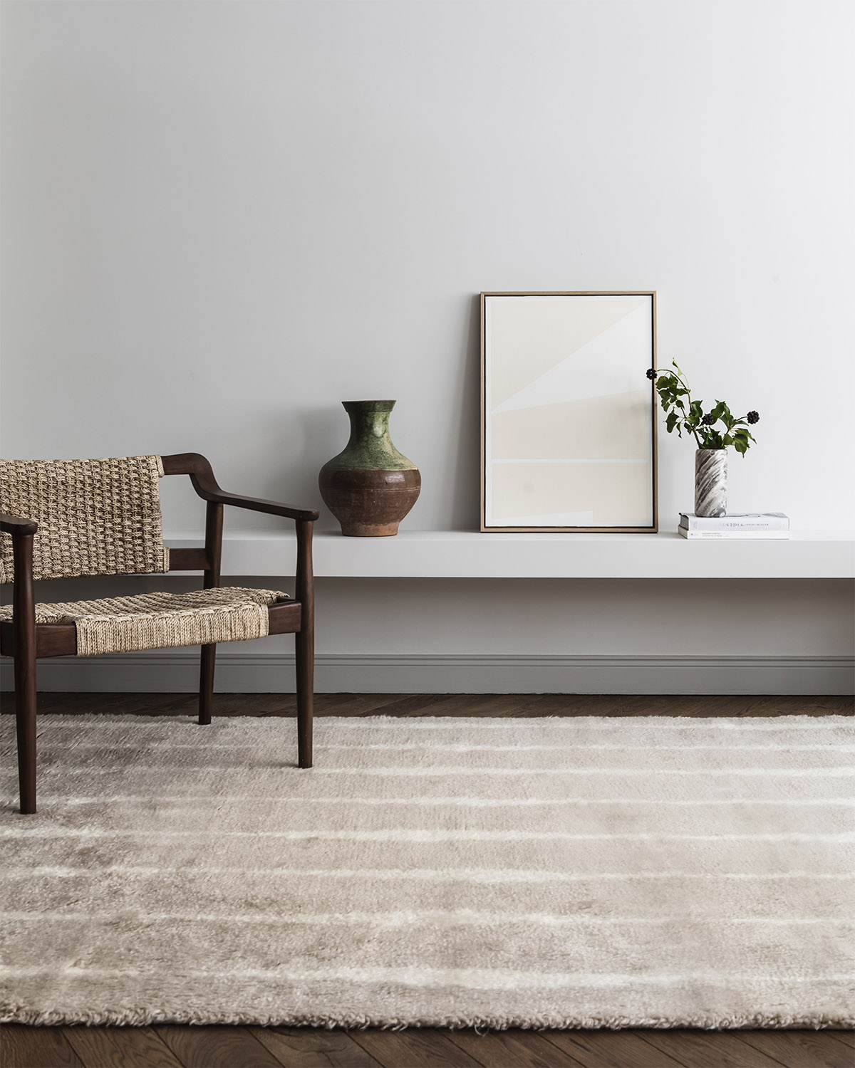 The shaggy Fjord rug in Pale Sand shown in a light living room setting together with a dark wooden chair with a woven seat.