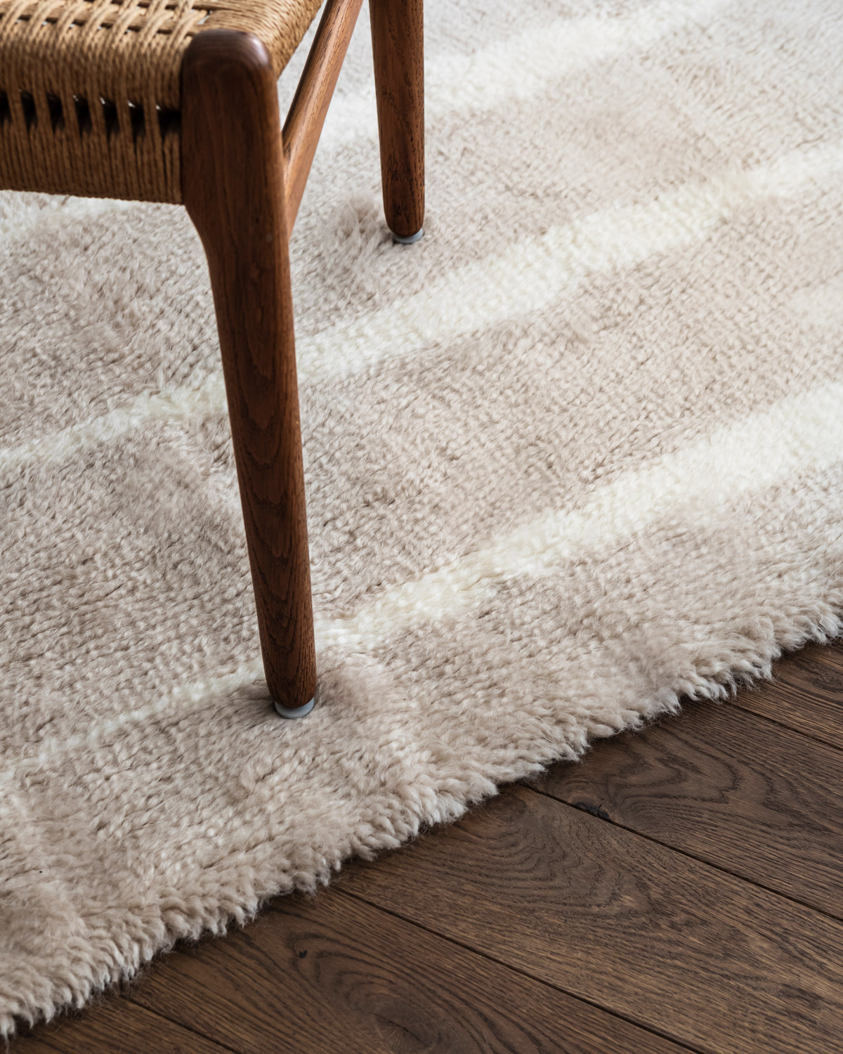 Close-up of the shaggy Fjord rug in the color Pale sand, showing the edge and texture of the rug.