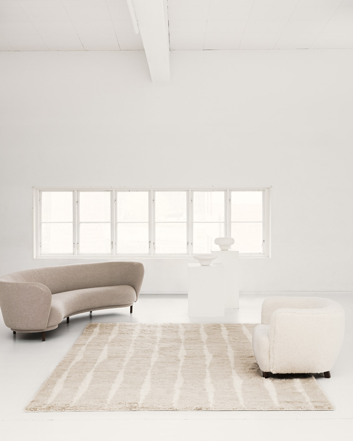 The Fjord rug in Pale Sand in a white, contemporary space together with a curved, beige sofa as well as a sheep fur armchair.