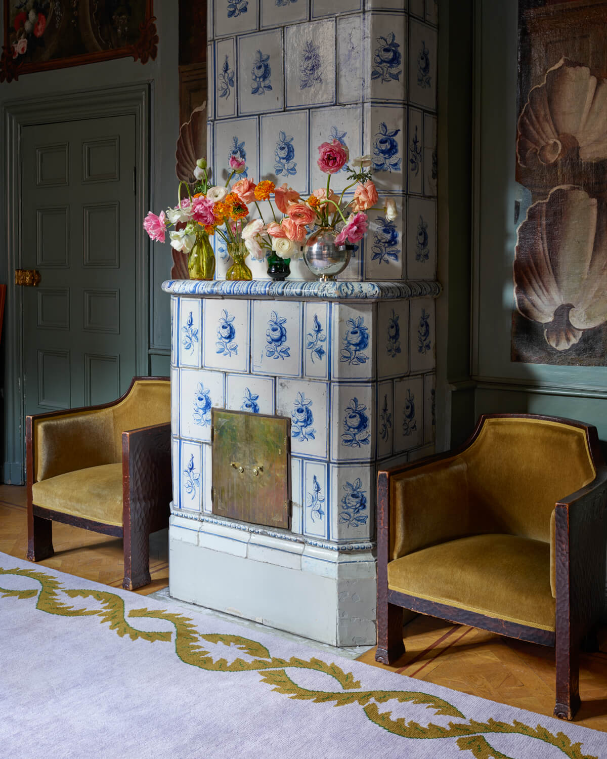Climbing Vine rug displayed in a beautiful room with an old, decorated tiled stove.