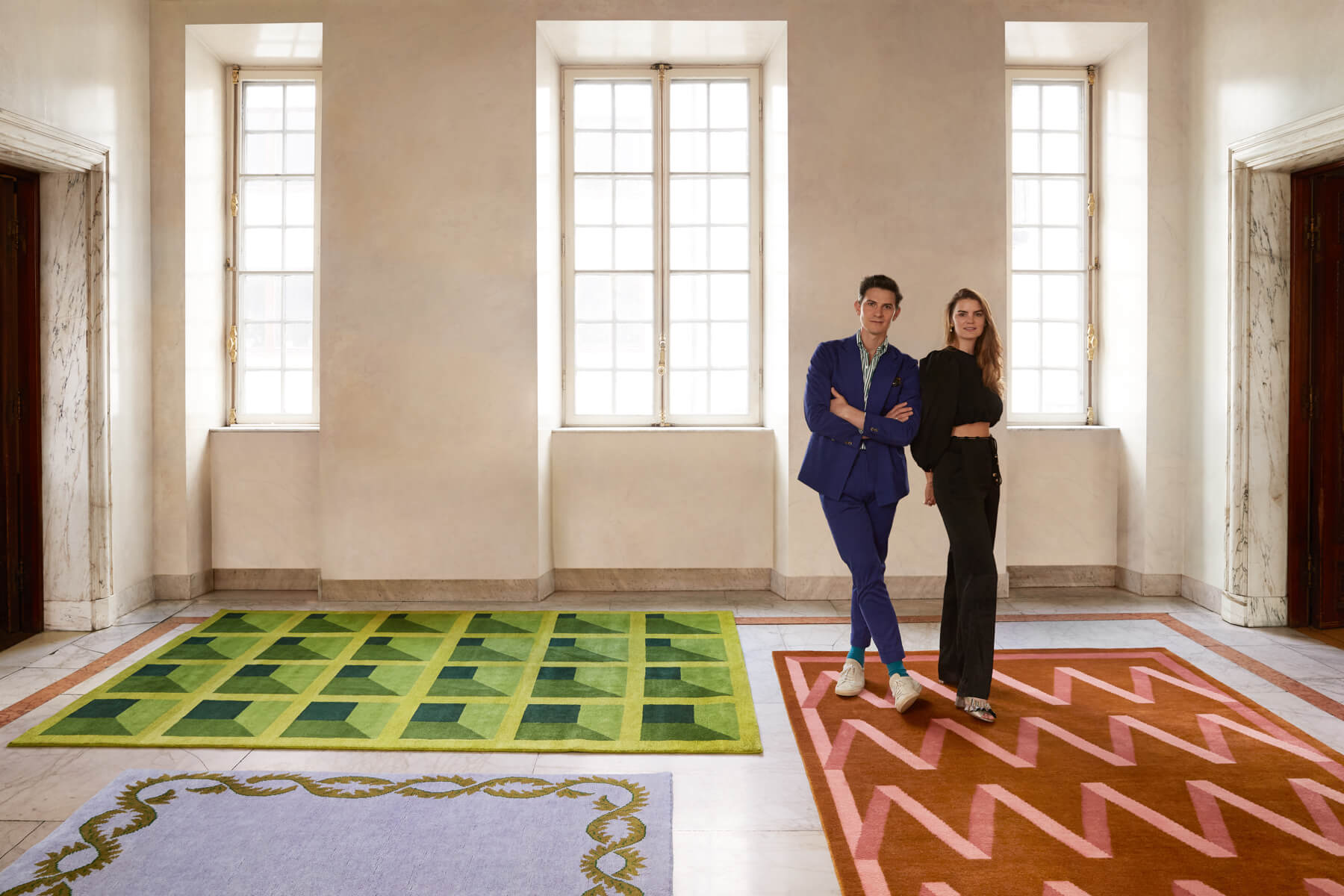 Design-duo Campbell Rey standing together with their rug collection.