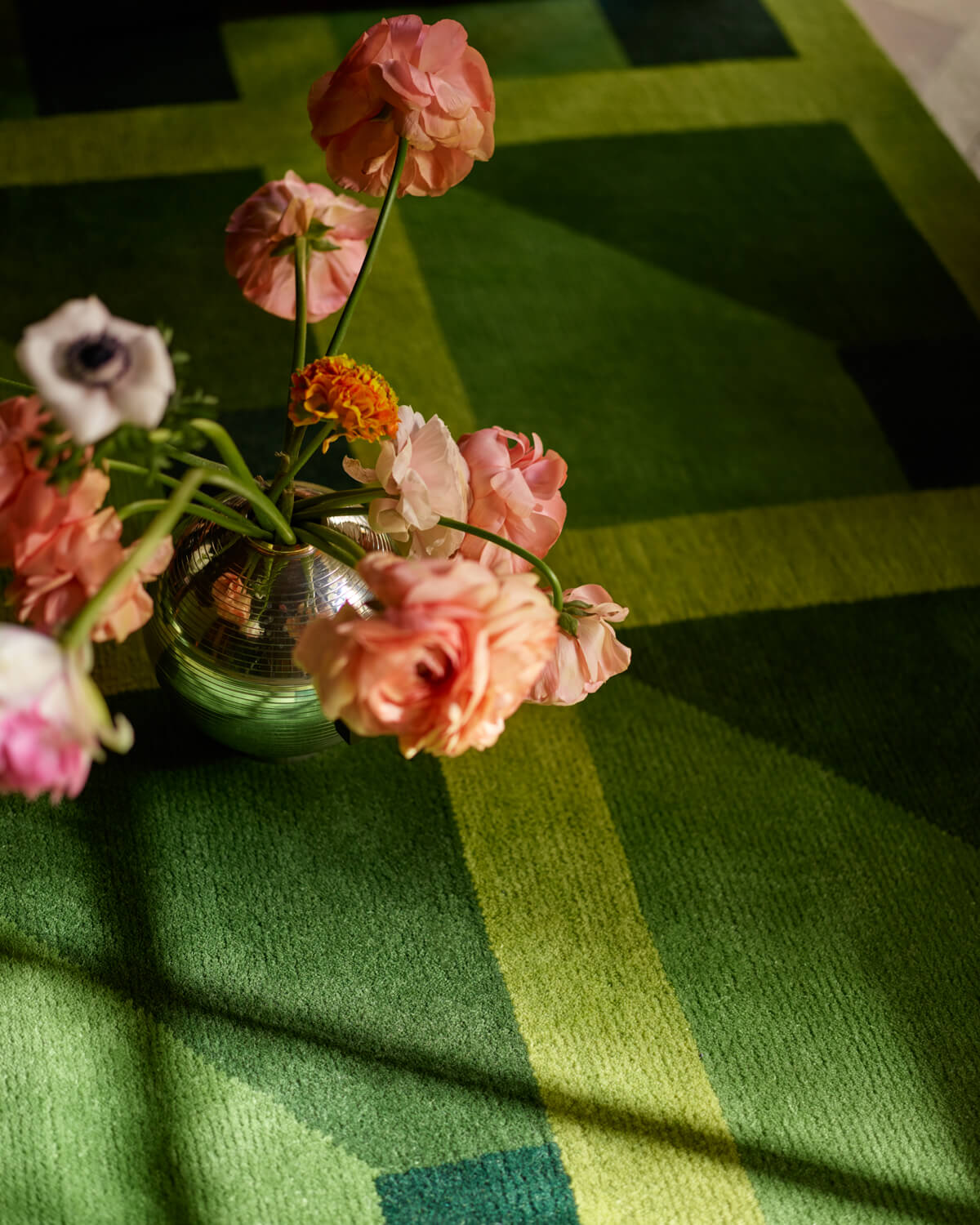 Close up of green rug Garden Maze with a vase of flowers.