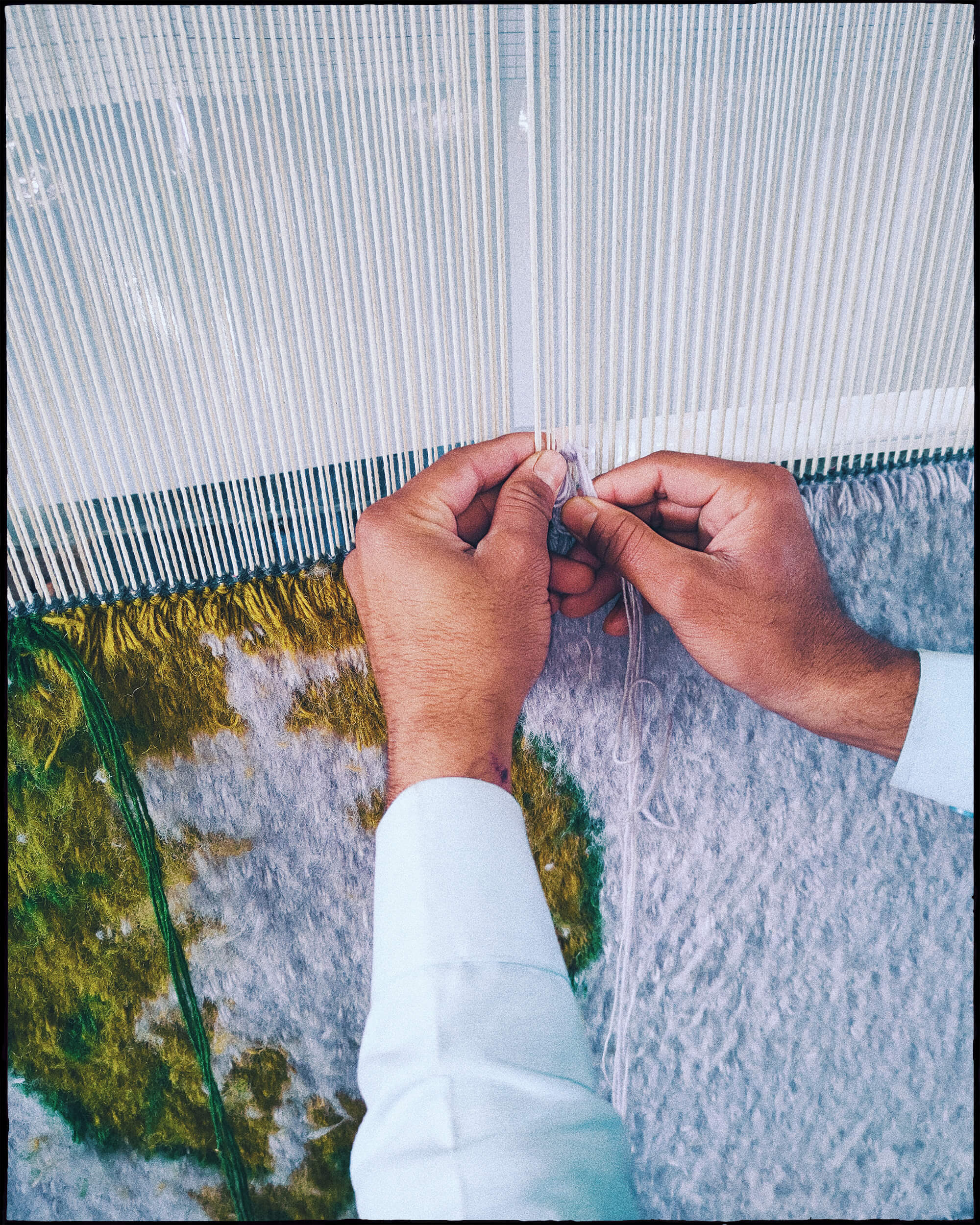 Close up of hands weaving a Climbing Vines rug.