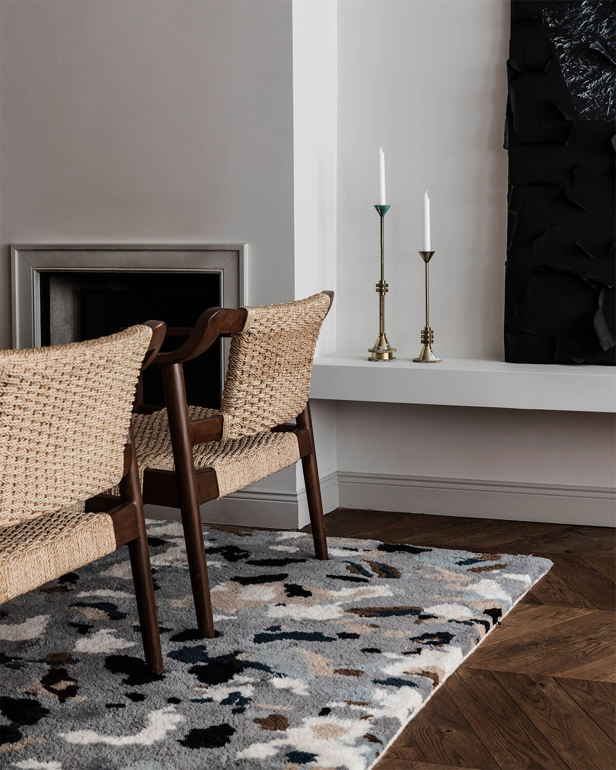 The Archipelago rug in Gray displayed in a nice, light living room setting. There us two armchairs in dark wood with woven backs and seats,