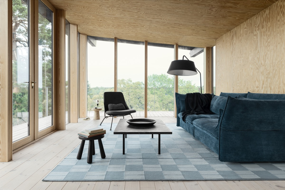Flatweave Båstad in Blue shown in a contemporary house with wooden walls, floors and ceilings. Decorated with a blue sofa and black coffee table.