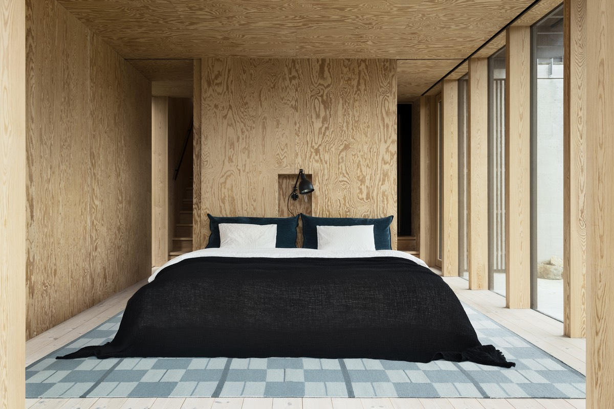 Flatweave rug Båstad in color Blue shown in a beautiful contemporary bedroom in the archipelago.