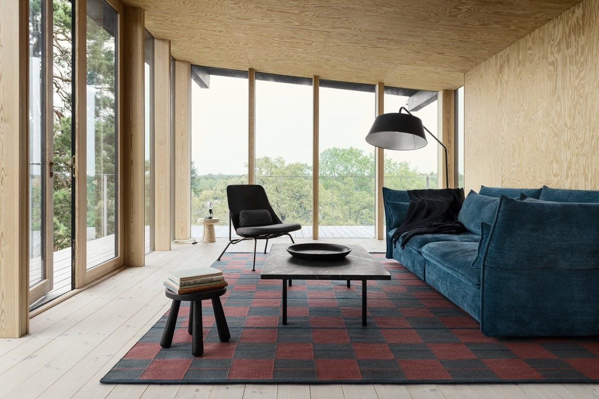Flatweave Båstad in Red shown in a contemporary house with wooden walls, floors and ceilings. Decorated with a blue sofa and black coffee table.