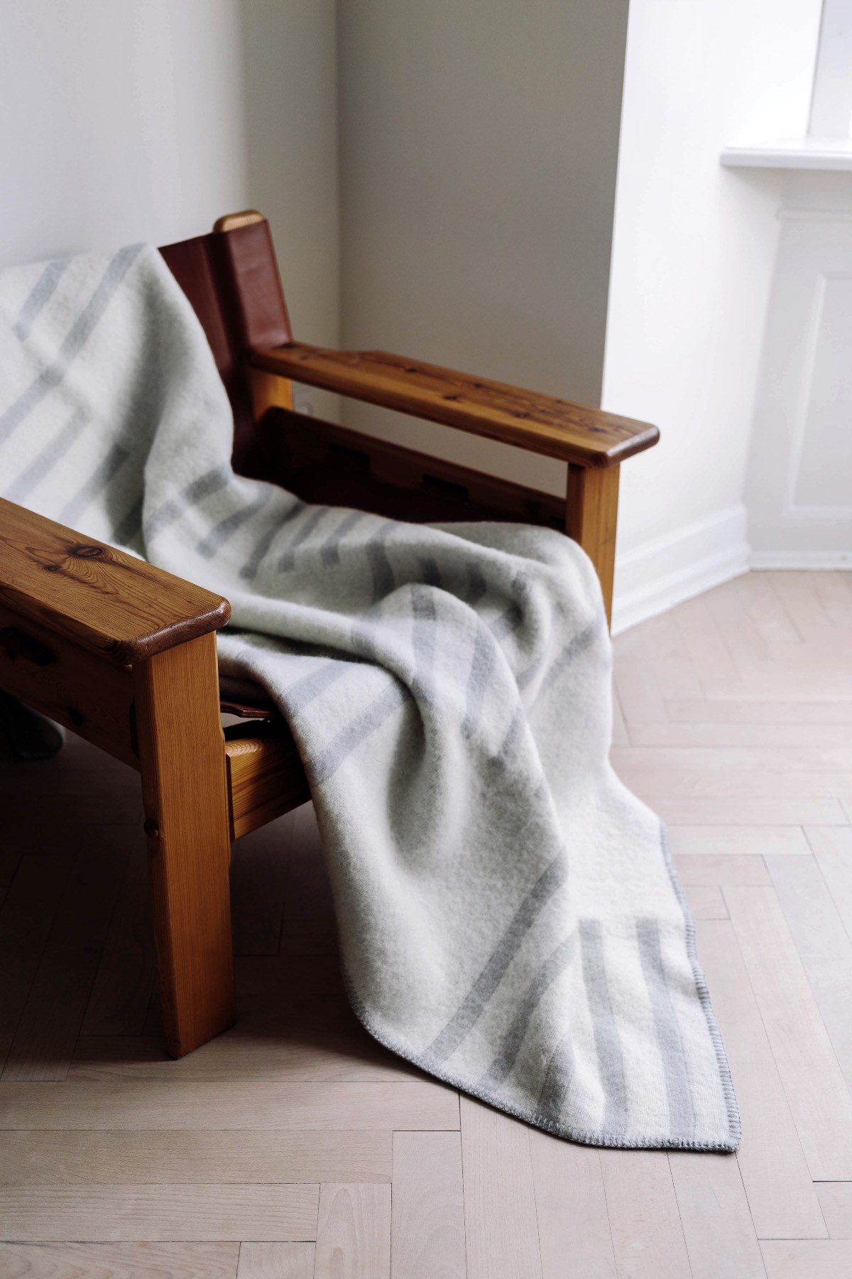 A cream and gray colored Classic wool blanket laying on a wooden armchair.