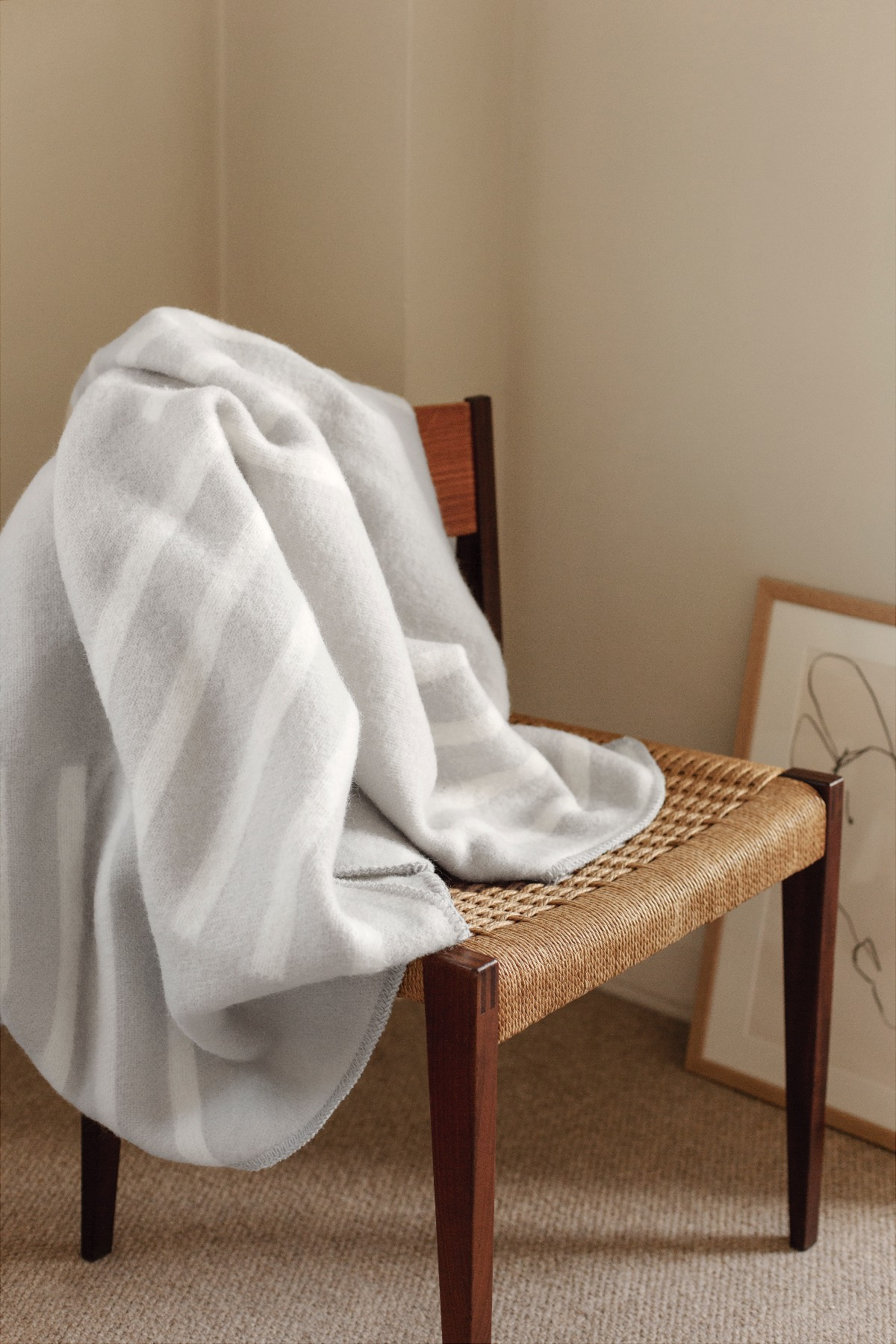 Wool blanket Classic in Cream and Gray hanging on a chair.