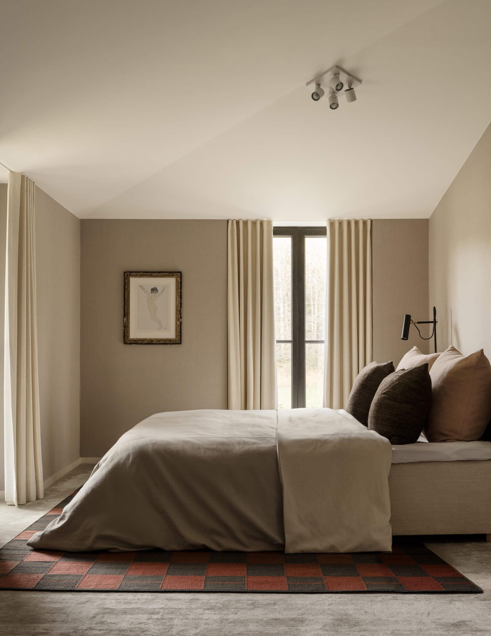 The Båstad flatweave rug in Red, in a beautiful warm beige bedroom.