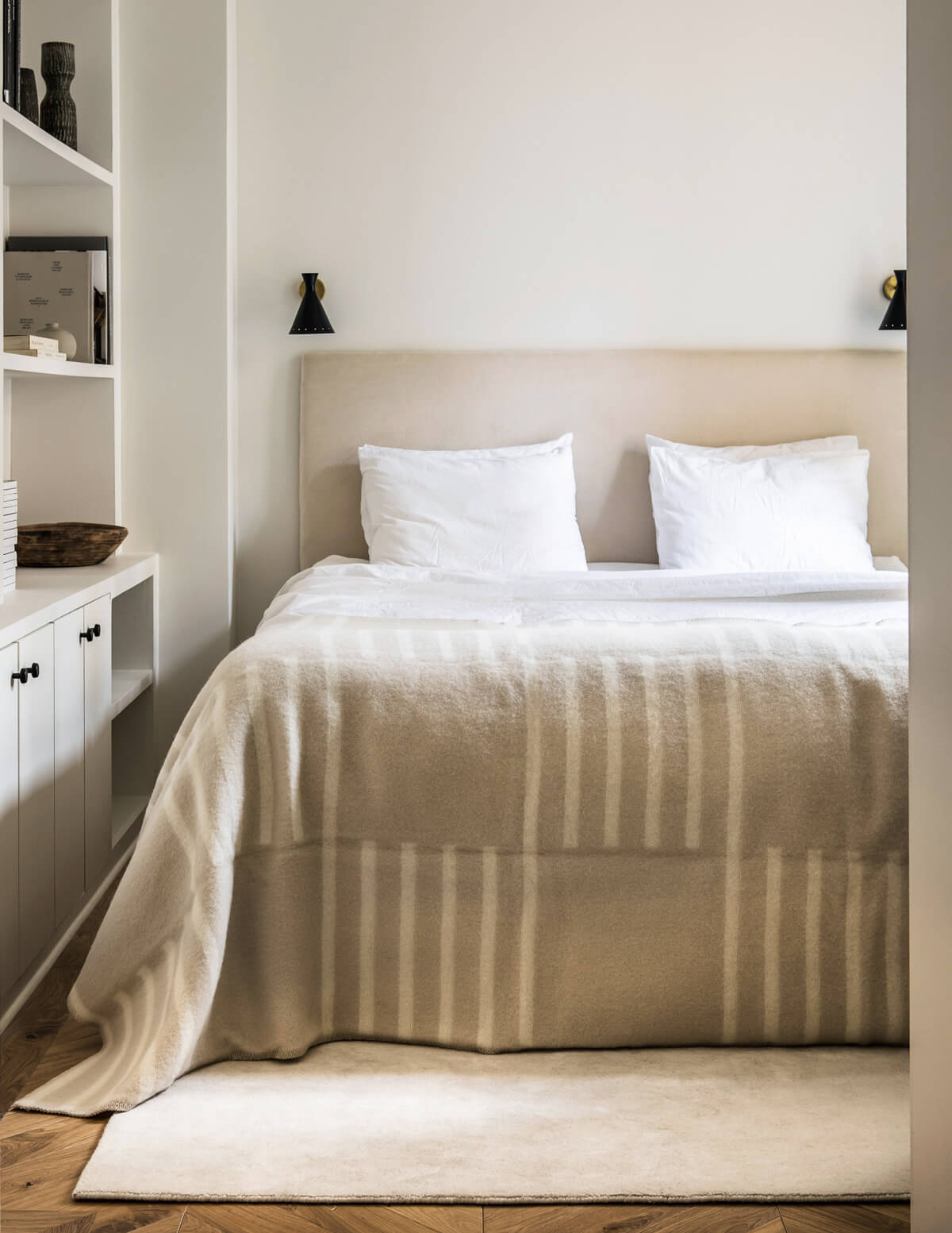 The Grand rug in Dusty White in a bright bedroom, with our Classic rug used as a throw on the bed.