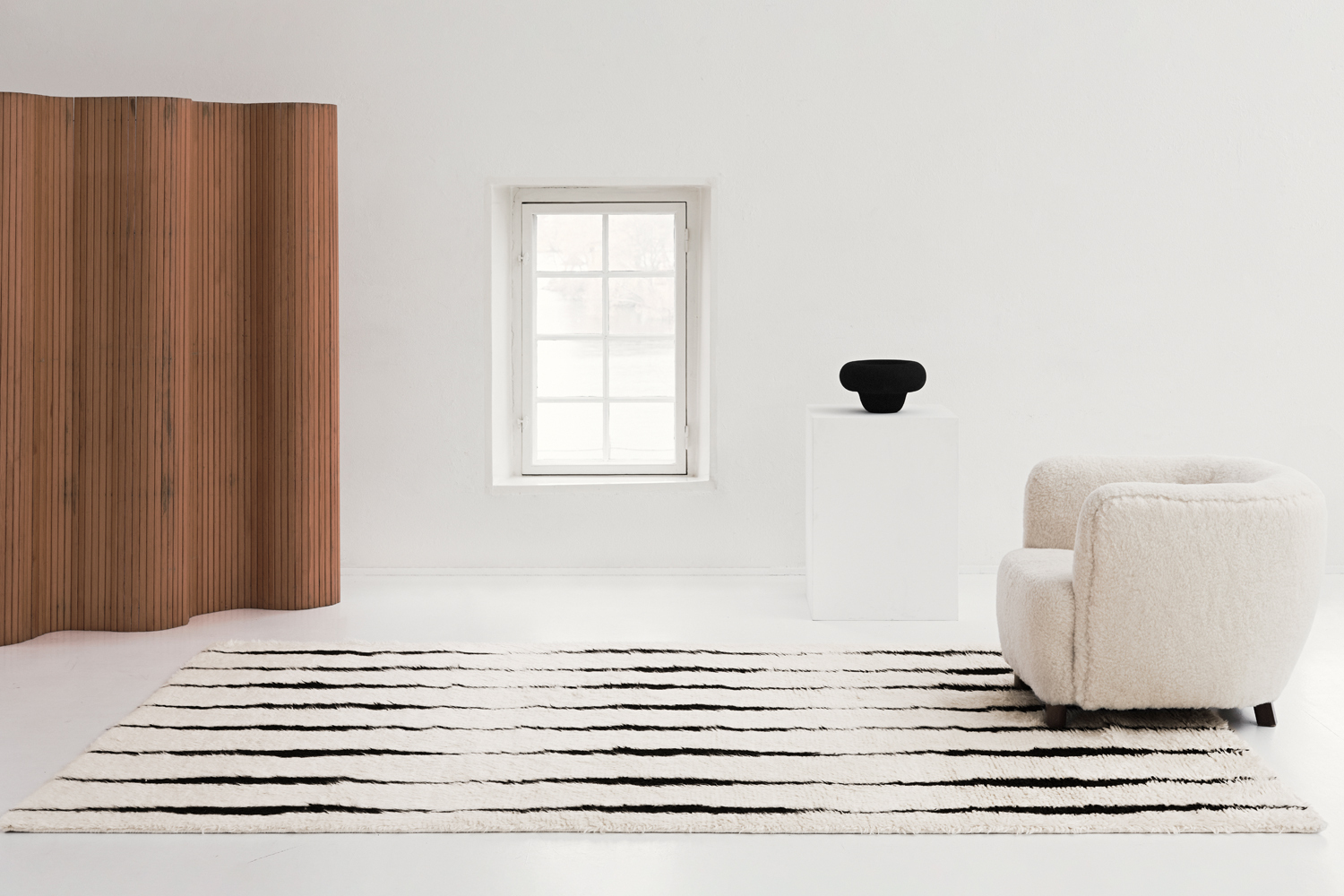The shaggy Cream colored rug Fjord is displayed in a white, gallery-like setting together with a white sheep fur armchair.
