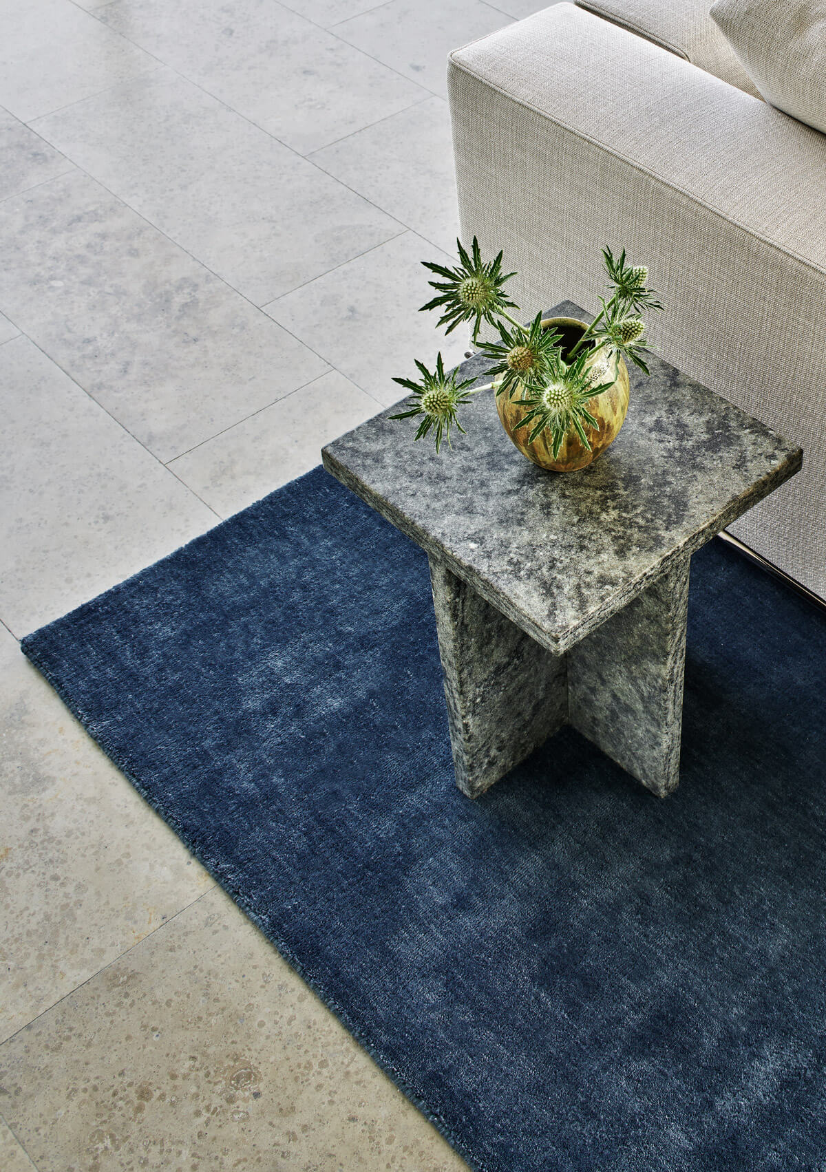 Grand in Deep blue displayed with a side table in stone.