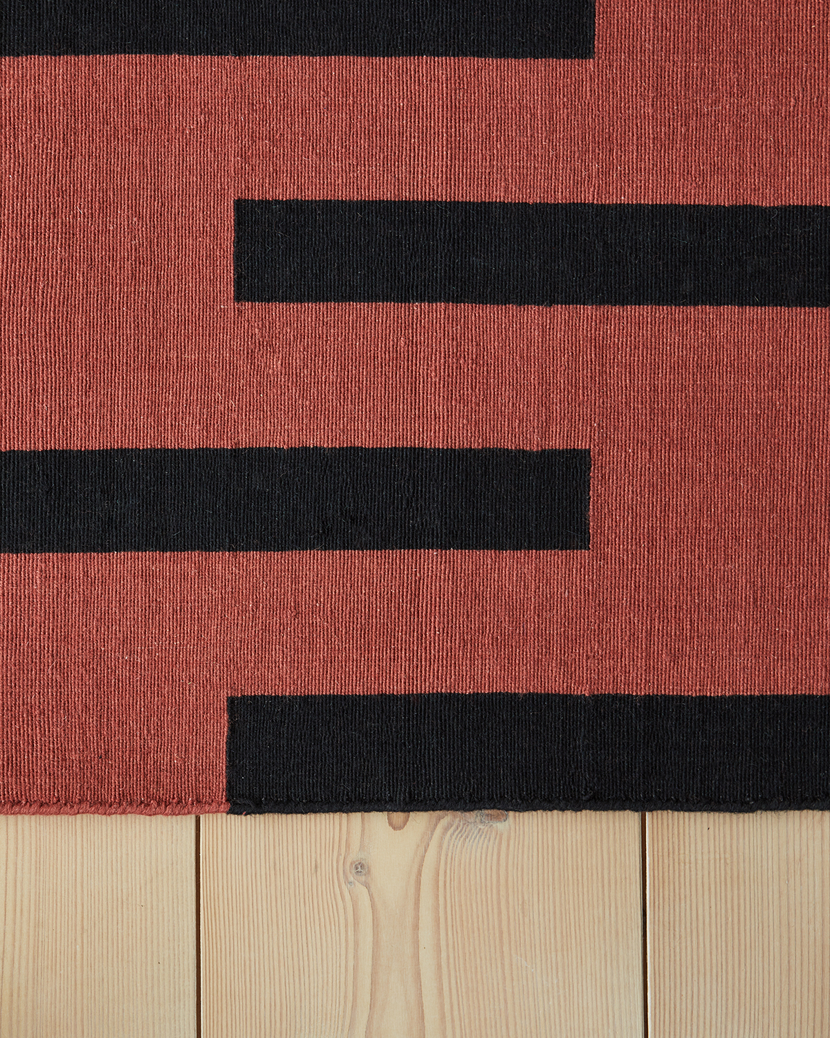 Close up of flatweave rug Tiger in color combination Red and Black.